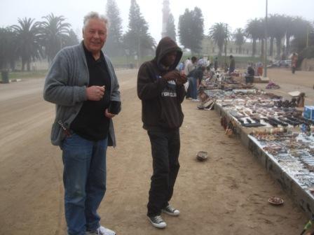 Jan-Ernst pruter så godt han kan på marked i Swakop. Her er det nøkkelringer som får navn på.