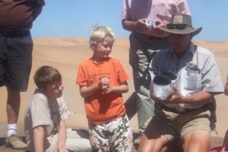 Sanden inneholder en del jern sulfat. Tommy demonstrerer med å dra en stor magnet over sanden, som suger til seg masse jern spon.