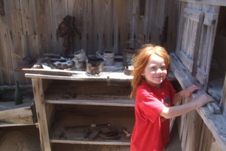 Emma- minstejenta hos naboen, sjekker gammelt husgeråd i en forlatt hytte i en gruvelandsby. Området ble svært utarmet på 70-tallet, da diamant forekomstene var store her.